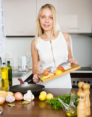 Smiling housewife cooking  soup from salmon in kitchen photo