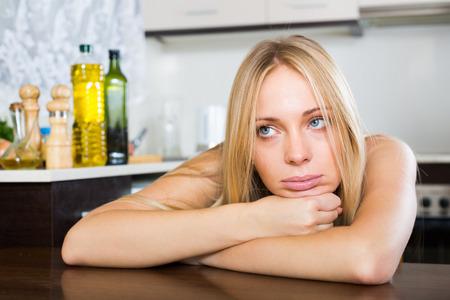 solter�a: Triste joven solitaria sentado en la cocina en el hogar