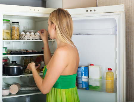 starving: Blonde  girl near opened refrigerator in kitchen at home