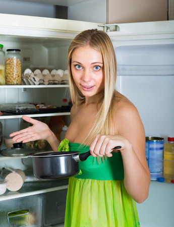 foul: Girl holding foul food near refrigerator at home