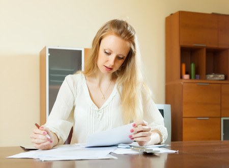 utility payments: serious long-haired woman fills in  questionnaire at home interior