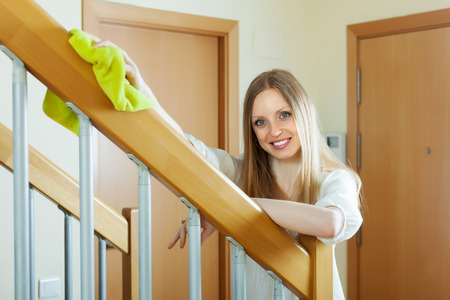 Happy  girl dusting stair railings at home Stock Photo