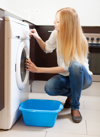long-haired huosewife doing laundry with washing machine at home photo