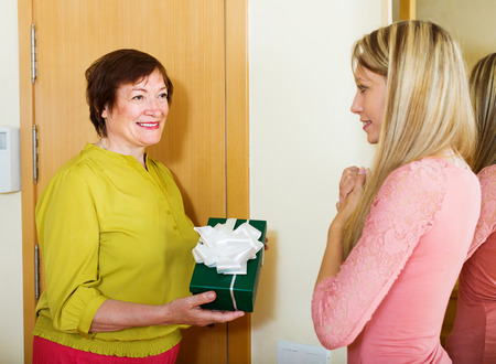 neighbor: Smiling mature neighbor presenting gift to young girl in home Stock Photo