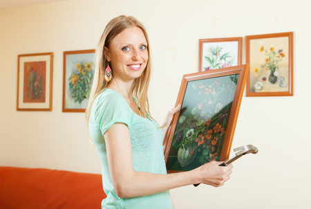 show case: Happy woman hanging the art picture on wall at house Stock Photo