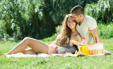 Happy  romantic couple sitting on grass at picnic in summer day photo