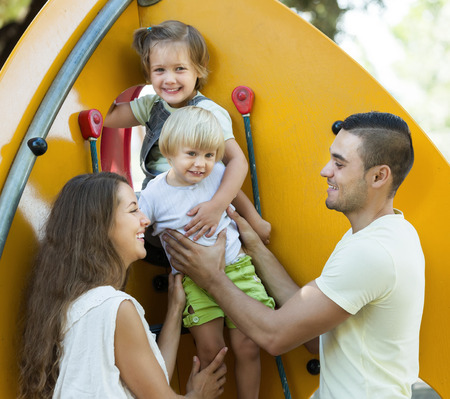 helping children: Smiling parents helping children on stairs at park Stock Photo