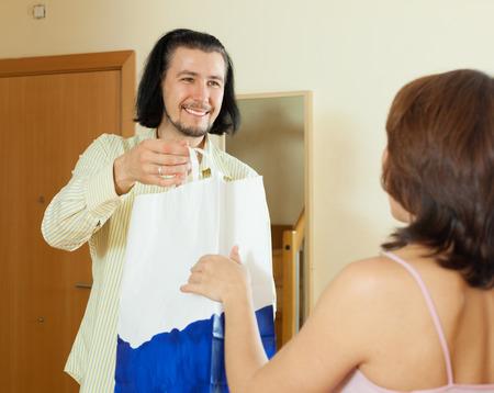 travelling salesman: Handsome salesman offering goods to women at home
