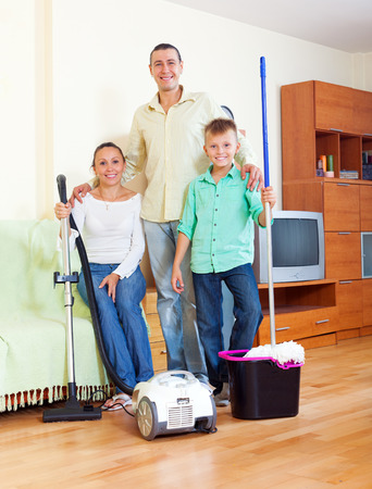 the weariness: Portrait of happy family of three finished cleaning in home
