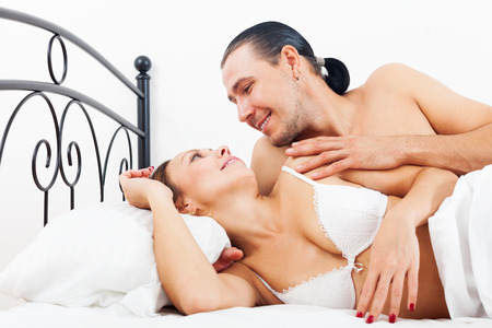 awaking: Loving adult couple awaking together on bed in home interior Stock Photo
