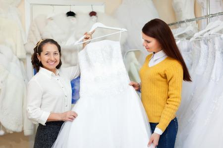 bridal gown: Ayudante de departamento ayuda a la novia en la elecci�n de vestido de novia en la tienda de moda nupcial