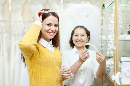 Shop assistant  helps the bride in choosing bridal diadem at shop of wedding fashion. Focus on girl photo