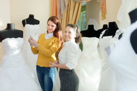 bride chooses bridal outfit at wedding store. Friendly shop consultant helps her photo