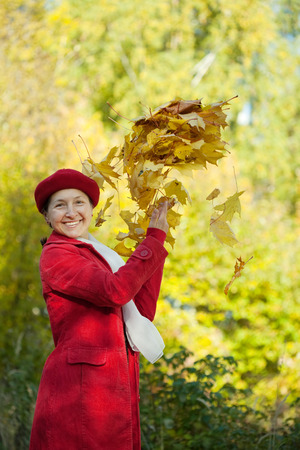 Happy mature woman throwing yellow maple leaves in the air in autumn photo