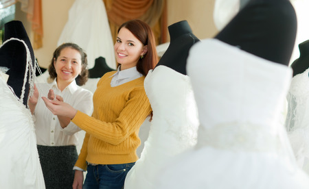 bridal salon: Shop assistant  helps to girl chooses white bridal outfit  at shop of wedding fashion. Focus on young