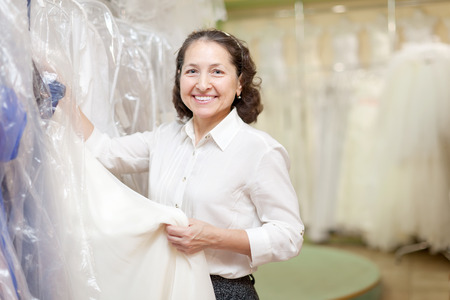 Shop assistant with bridal dress at wedding store photo