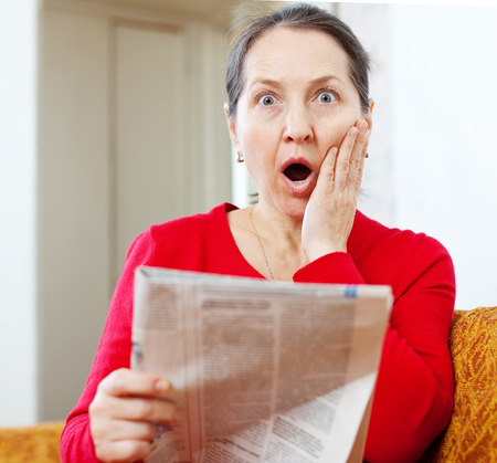 mirth: Mature surprised woman with newspaper at home