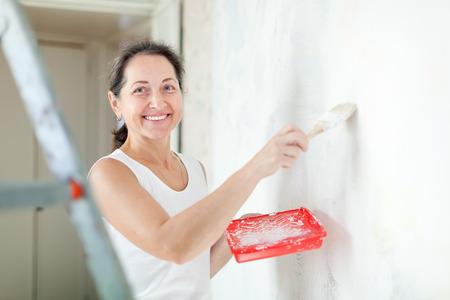 housepainter: Happy mature woman makes repairs at home