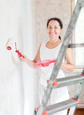 home repairs: Happy mature woman makes repairs at home