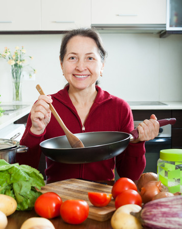 fryingpan: Smiling mature woman cooking  with skillet in domestic kitchen