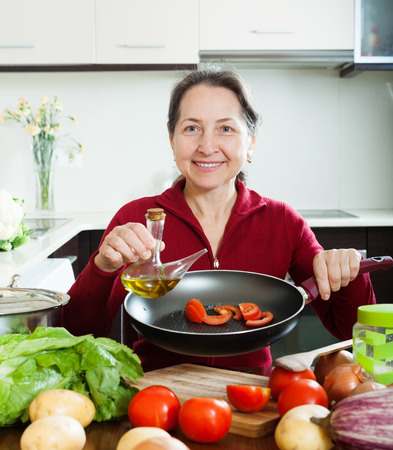 Smiling mature woman pouring oil into fryingpan at home photo