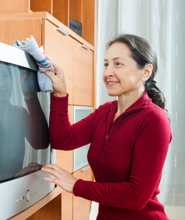 dusting: mature woman dusting TV at living room Stock Photo