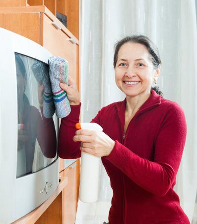 tele: Ordinary mature woman rubbing TV at home
