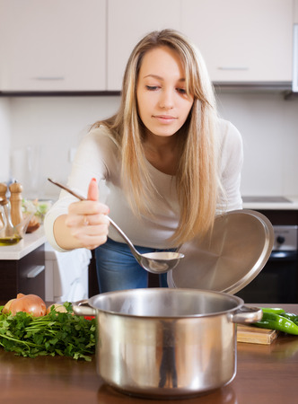 ordinary woman: Ordinary woman cooking  soup in kitchen