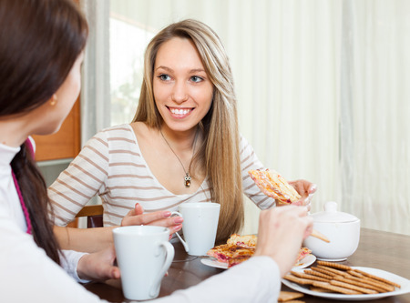 happy girls  drinking tea and gossiping in home photo
