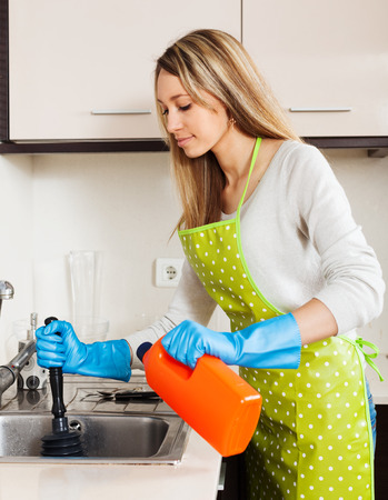 Young housewife cleaning pipe in kitchen at home photo
