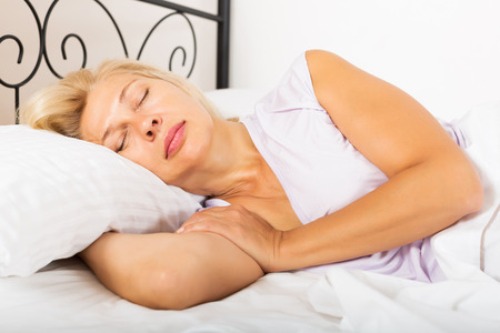 Blonde mature female in pajamas sleeping with white pillow in bed at home photo