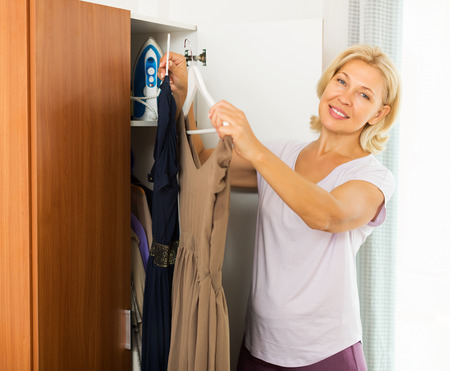 get dressed: Mature smiling woman at wardrobe. She thinking what get dressed