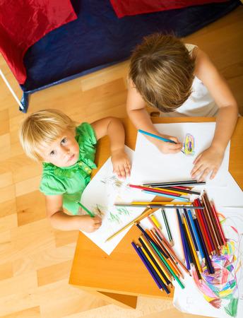 2 to 3 years: Due bambini schizzi con carta e matite in home interior Archivio Fotografico