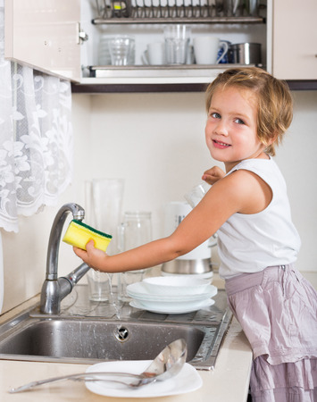 Cute little girl cleaning dishes in the kitchen photo