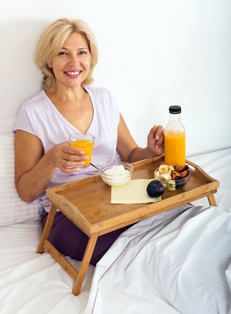 Happy mature woman enjoying  breakfast in bed photo