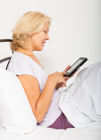 blonde mature woman with eBook laying in her bed at home photo