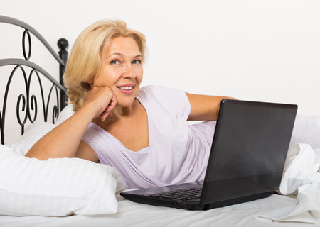 Smiling mature woman with laptop on white sheet in bed at home