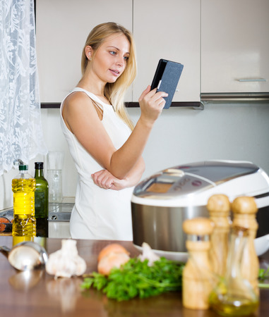 housewife reading ereader and cooking with multicooker at home interior photo