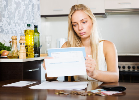 serious blonde girl with money and documents in home interior
