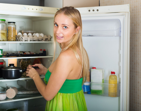 refrigerator kitchen: Blonde long-haired girl near opened refrigerator in kitchen at home