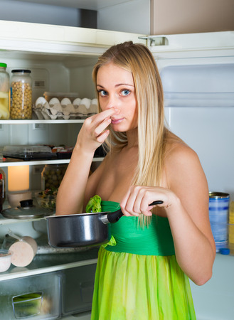 Girl holding her nose because of bad smell from food near refrigerator at home photo