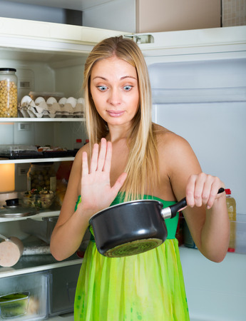 frowy: Young woman holding foul food near refrigerator at home