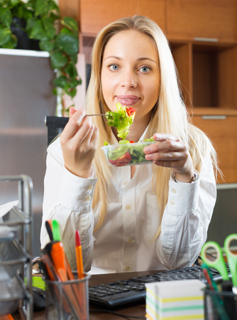 overworking: Smiling young blonde woman having healthy lunch at office desk Stock Photo