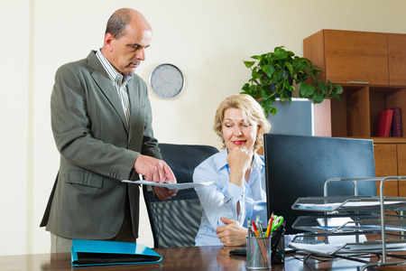 to the secretary: Senior office manager scolding elderly female secretary for mistake Stock Photo