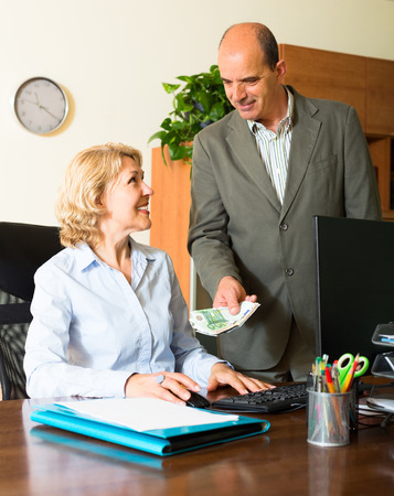 Smiling female secretary receiving from boss salary in cash