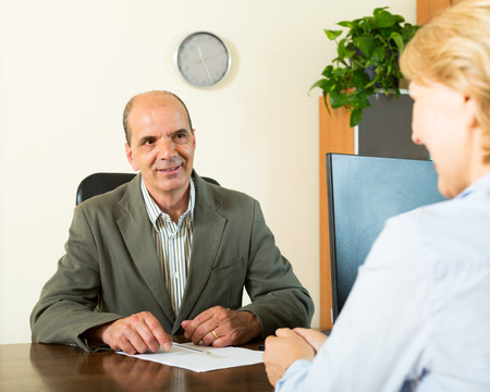 Happy client talking with manager at notarys office
