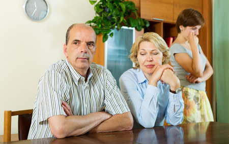 fracas: Mature parents with  adult daughter having conflict  in home interior Stock Photo