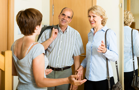 Happy aged family couple visiting adult daughter at home