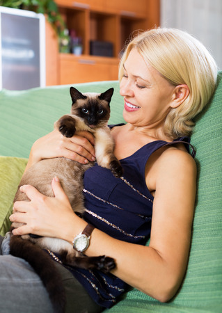 Portrait of mature woman sitting on sofa with her cat at home photo