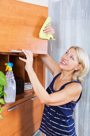 Housewife cleaning cabinet with rag at home